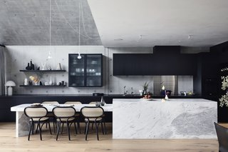 The kitchen island and attached table are a custom design in a natural stone called Elba Blue Marble.