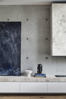 In addition to outfitting the home with furnishings, Kennon also selected the artwork. Here, a painting by New Zealand artist Matt Arbuckle rests on a low built-in storage cabinet clad in Tundra Mist Natural Stone, a material that provides texture against the tonally similar concrete walls.