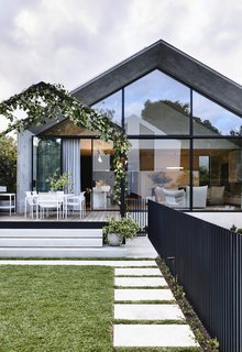 """The back of the home and its soaring glass-and-concrete addition create a strong connection between the indoor and outdoor spaces, and the rear garden and the pool feel like """"a secret refuge."""""""