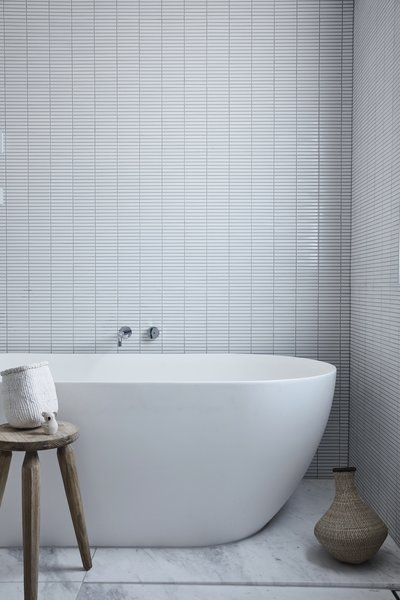 A ceramic soaking tub is paired with an antique wooden stool found in a local market.