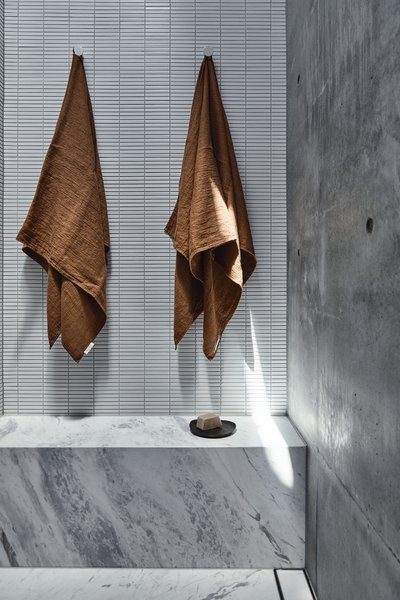 The shower features a bench and is a mix of Elba Blue Marble, Inax Yohen Border tiles, and concrete.