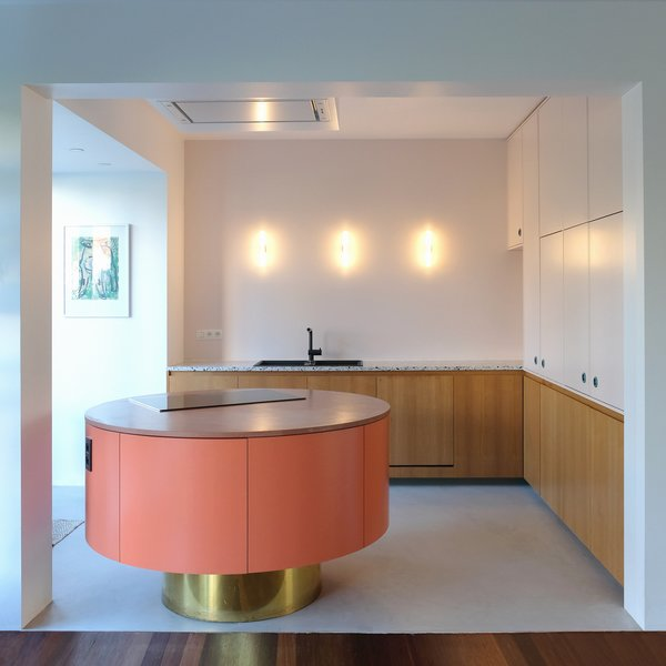 Otten opened the kitchen of this midcentury home in the suburbs of Antwerp and inserted a custom-made kitchen island with a pink concrete countertop and electric cooktop range. Pastel shades paired with wood and brass make the salmon-colored island pop.