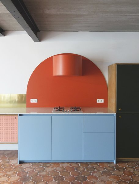 "The kitchen, which is meant ""not to look like a kitchen"" is composed of art deco-inspired shapes, such as this bold, red circular form that Otten created to wrap an ordinary range hood. Even the oven is hidden behind the custom cabinets."