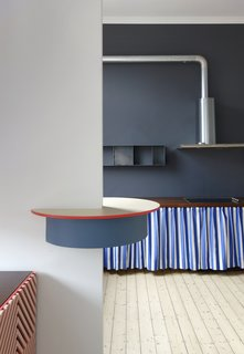A table top-like breakfast bar designed by Otten is inserted in the wall to divide and connect the spaces.