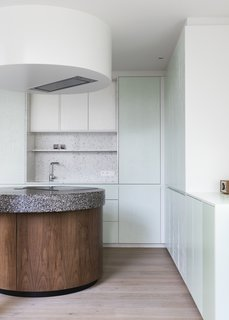 "Otten chose a light color palette of soft green lacquer set against sandblasted pine veneer to keep the space looking as fresh as possible. ""The round form on the ceiling is just to hide the cooking hood,"" he says."