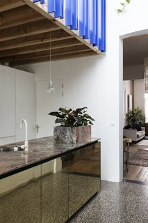 """The planter box was an excuse and a solution to integrate the electric plugs on the counter,"" shared Otten. The stunning slab of pink marble which serves as the island's countertop is the result of a trade between the client, an artist, who traded a work of art for it with the art-collecting owner of Vandeweghe, the marble company, where the beautiful slab of pink marble is from. Brass cabinet doors reflect the terrazzo flooring from Bomarbre."