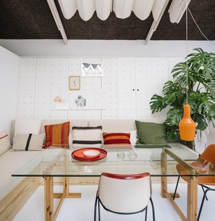 """""""Everything is located around the perimeter to create as much usable space as possible,"""" says de la Vega. The firm designed the banquette to do double duty as a storage trunk, and the wall hides custom-made closets with holes for hanging paintings and models. The vintage chairs are by Eero Aarnio for Asko."""