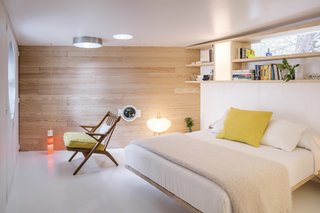 The bedroom features a feature wall, built-in bookshelf, and bed made from pine. All of the furniture is custom made except for the vintage French folding beach chair.