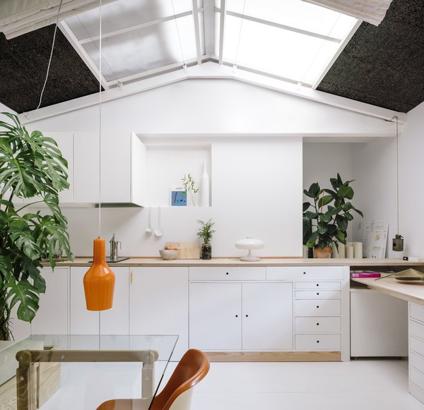 The former painting studio is now a multipurpose kitchen/dining/living/office space. Woodworking accounted for a major portion of the renovation budget—many of the furnishings were custom made using either pine or birch plywood (as seen in the countertop and office table).