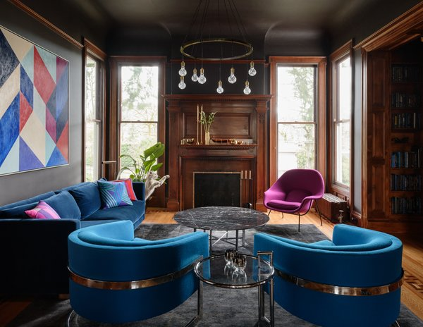 In the richly hued living room, a Milo Baughman coffee table with a chrome base and custom marble top pairs with Milo Baughman barrel chairs that have been reupholstered in a saturated blue fabric. A custom velvet sofa adds another textured layer. A custom light fixture with crystal bulbs from The Future Perfect hangs like jewelry above the space, and a geometric painting by senior JHID designer Chelsie Lee ties the colors together.