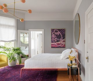 The master bedroom was painted a soothing shade of pale gray with white ceilings and doors. Peach, fuchsia, and purple tones create a dynamic contrast in the form of a vintage, overdyed rug from Rug Knots and a painting by Amelia Midori Miller. The Urbino bed in copper is from Property Pendant, and the Line Pendant 06 light is from Douglas and Bec.
