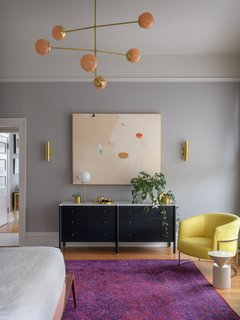 Allied Maker Court Sconces pick up brassy tones from the lighting and highlight a peach-toned, abstract painting from Jen Winks Hays. A pair of vintage Milo Baughman barrel chairs further brighten the space with their sunny shade of yellow.