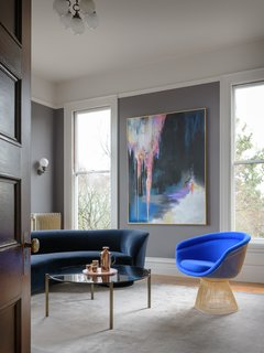 The home office  is a showcase for an electric blue Warren Platener lounge chair from Hive Modern, paired with a vintage Vladimir Kagan Serpentine Cloud sofa. The painting is by Michelle Betancourt.