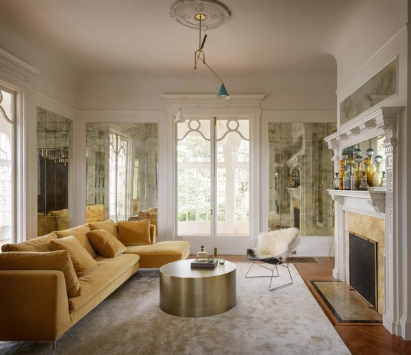 The addition of the antiqued mirrored panels amplifies natural light that the living room receives from the adjacent sunroom.