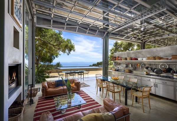 The kitchen of the main house overlooks a lap pool on the roof of the guesthouse and the Pacific Ocean beyond.