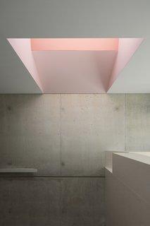 粉红色调的天窗和阅读角落动画现浇混凝土楼梯墙。