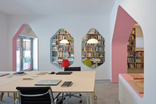 At the entrance, a meeting space can be converted into a gallery showcasing the studio's lighting collection. Playful hexagonal windows separate the meeting area from the workspace, and a chunky pink structural arch leads to a display and storage niche.