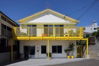 "The facade features a sunny yellow balcony—intended to spark a smile, but it's also a statement by the architects against the ""monotonous and dull color palette"" of traditional Japanese neighborhoods."