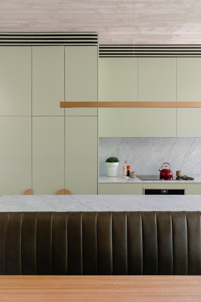 Carrara marble countertops and backsplash add a luxurious feel, as does the dark green leather upholstery on the bench seating which, in a space-saving move, is essentially part of the kitchen island. The Highline linear pendant light is from Archier.