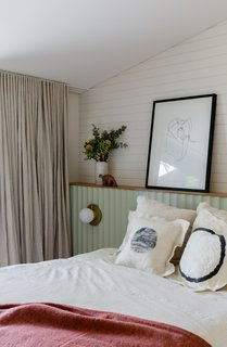 The master bedroom features a scalloped, light green headboard lined in Porta timber moldings.