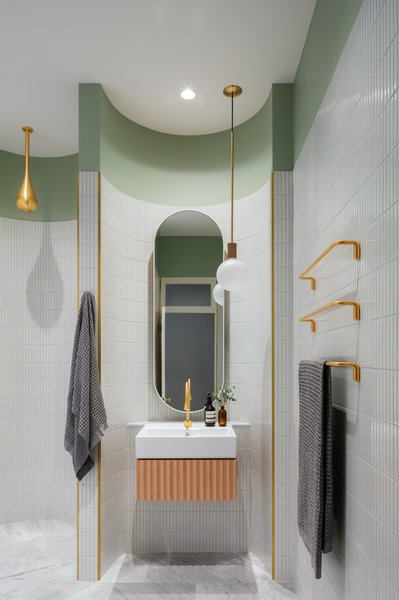 "The brass fixtures are from Gessie's GOCCIA series. Brass borders add ""a sharp edge to the tiled, curved spaces."" The scalloping appears in this space on a large deconstructed scale as well as in the curved detail of the floating vanity."
