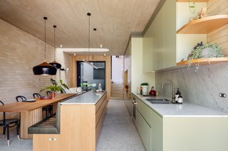 The kitchen features custom timber furniture, Tasmanian oak cabinetry, and custom cabinetry finished in Dulux White Cabbage. The pastel green hue complements the forest-green, leather bench seats and nods to the original kitchen's former color.