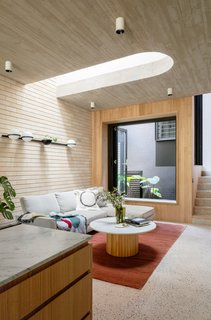 "There are many textures at play in the living room—the board-formed concrete ceiling, the light brick wall, wood paneling, and the terrazzo floors. ""The texture of the timber is reflected in the concrete,"" says Peake. The lightwell adds an additional internal light source and another spot to insert greenery. The Vibia Palma wall sconce from Koda Lighting is affixed to the wall over the sofa."
