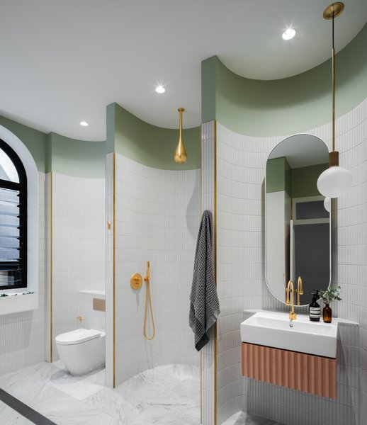 "The spacious main bathroom (a former bedroom), joins marble, brass, and green elements. It is innovative for its use of ""micro-spaces"" that are subdivided and contained within the scalloping of the rear wall. They are meant to make each element feel special and separate, dividing a large room into smaller spaces that ""hug you as you use them."""