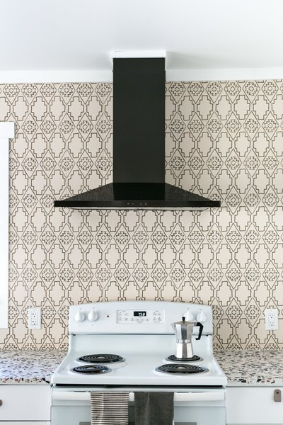 The ceiling panels were replaced with smooth painted drywall, and funky terrazzo countertops from Concrete Collaborative replaced granite. The chic, black-steel range hood is from Anzio.