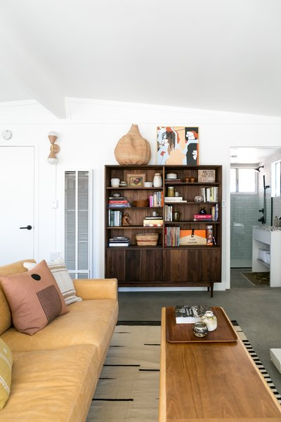 The Grove Modern bookshelf is from Room & Board, as is the tan leather sofa and the rug.