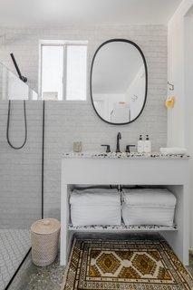 娜塔丽调整了卫生间和淋浴间的位置,并增加了一个新的梳妆台,配上水磨石台面,与厨房里的梳妆台相匹配。从地板到天花板,都铺着Ann Sacks设计的砖样的泥瓦匠场地瓷砖。