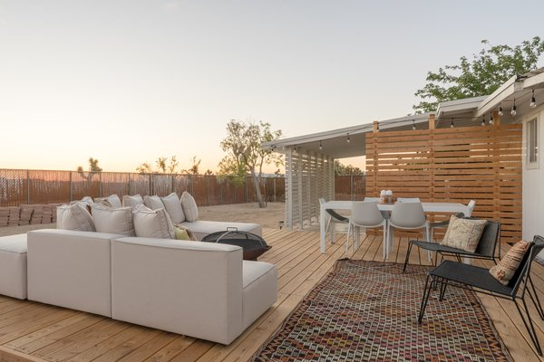 """""""Adding the large wood deck to extend the living spaces outside was a game-changer,"""" shares Natalie. """"We now have another living room and dining area to take advantage of in the evenings."""" The Oasis modular outdoor sofa and black Penelope lounge chairs are from Room & Board."""