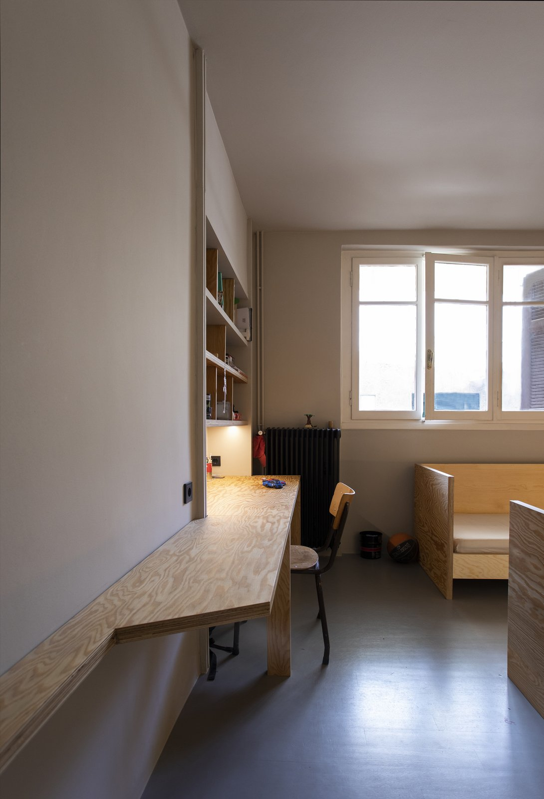 Bedroom, Chair, and Bed The custom desk maximizes the available square footage.  Photo 10 of 13 in A Crisp Athens Apartment Makes Room for a Family's Home Brewery