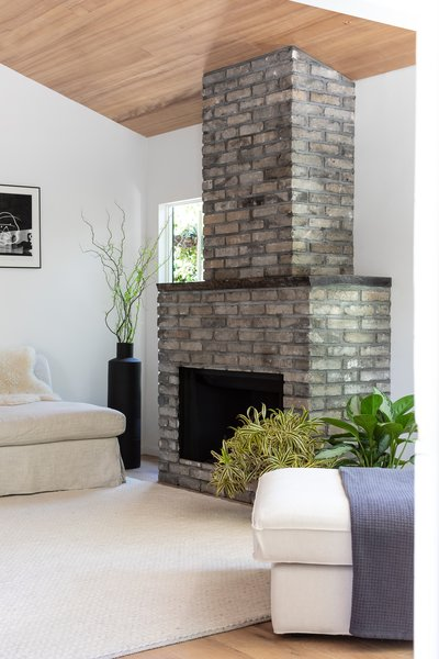 Nwankpa Gillespie built out the fireplace with dark bricks that add texture and contrast with the tongue-and-groove ceiling.