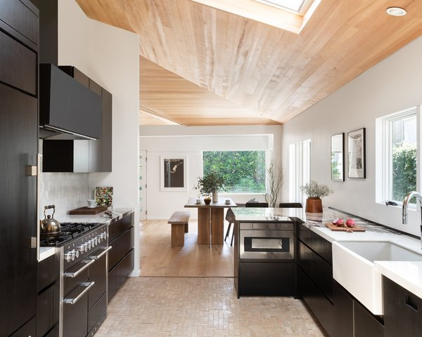 The dark wood kitchen cabinetry contrasts with the light wood paneling and terra-cotta tiles.