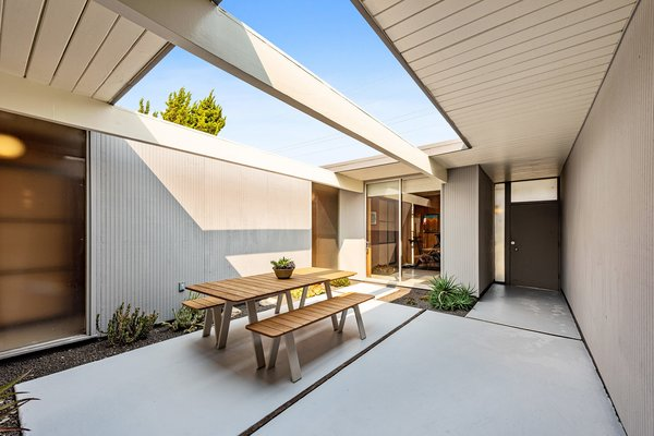 The home opens to a sleek central atrium with wide concrete pavers and room for alfresco dining.
