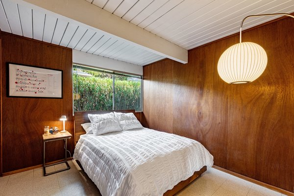 The second bedroom is wrapped in warm wood paneling and has a Nelson ball wall sconce.