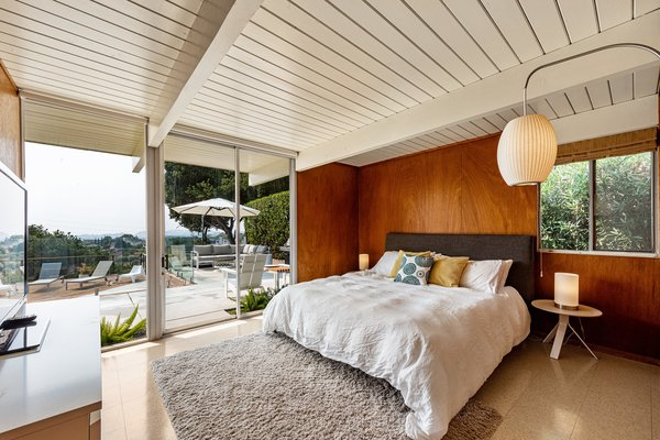 The main bedroom has glass sliding doors that lead out to the pool patio. There are warm wood walls, a period-appropriate Nelson cigar wall sconce, and an ensuite bathroom.