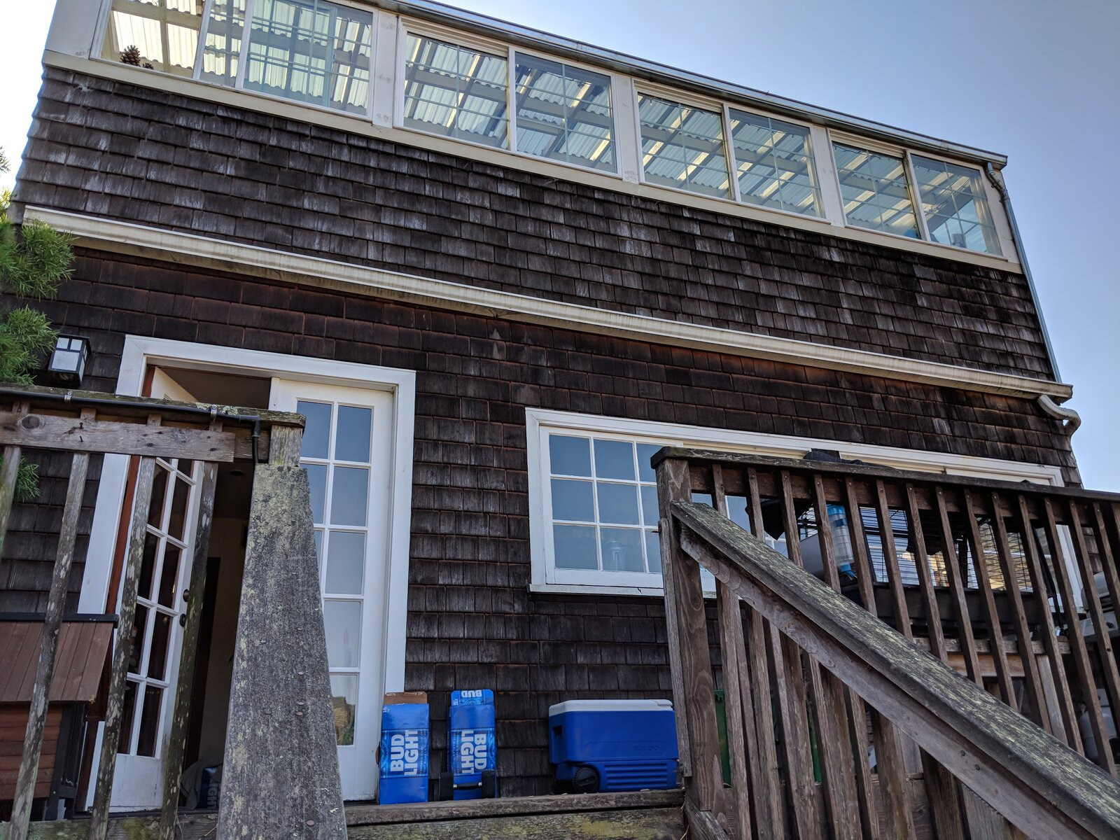 Before: The back of the home had a second-floor balcony off the kitchen with a sunroom above it. The balcony was taken down, and the sunroom was enclosed.   Photo 4 of 18 in Budget Breakdown: A Former Berkeley Commune Is Surgically Renovated for $944K