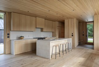 """""""The wife's vision was to create a very calming interior using a minimalist material palette,"""" explains Mac. """"The custom kitchen was designed to be elemental—we wanted [it] to feel more integrated [with the rest of the space]. The oak cabinets, concrete countertops, and appliance placements all reinforced this aesthetic."""""""
