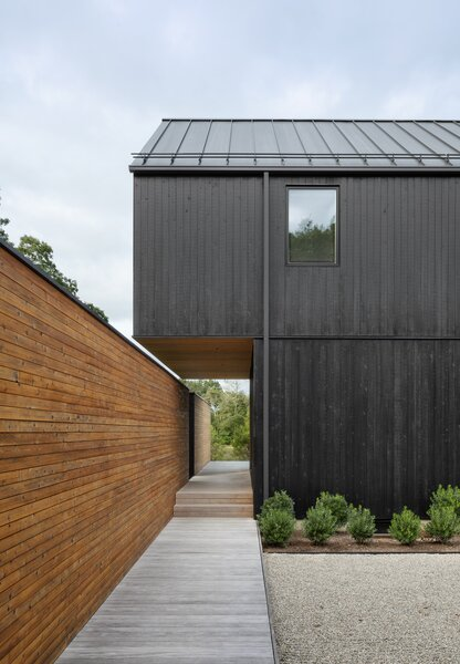The black-stained gable cantilevers over the entryway and aligns flush with the landscape wall, creating a horizontal gap that intersects with the vertical space between both walls.