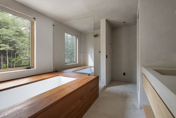 """The primary bathroom features brass fixtures and teak details that are accentuated by a smooth plaster finish. """"The continuity of the finishes creates visual balance within the space,"""" says Mac."""