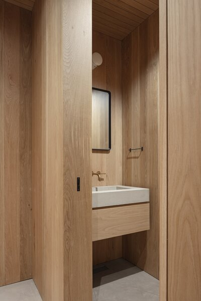 The bathroom's warm, natural finishes include a brass faucet and wood paneling.