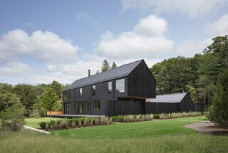 The 3,275-square-foot home is composed of two separate black gable volumes: a two-story main house and a one-story garage.