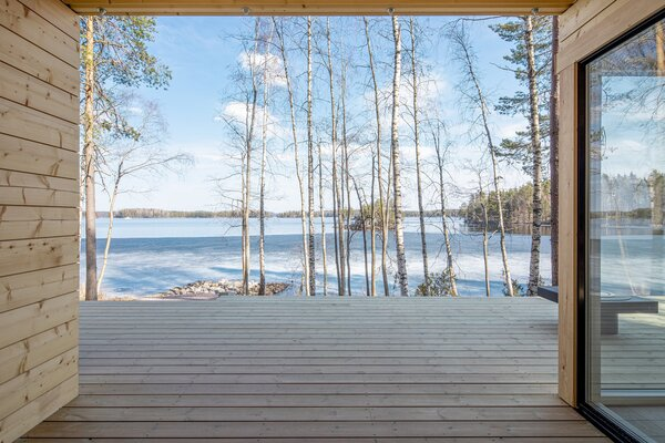 At the center, the two volumes are separated by a wood deck that overlooks a large lake called Ruotsalainen.