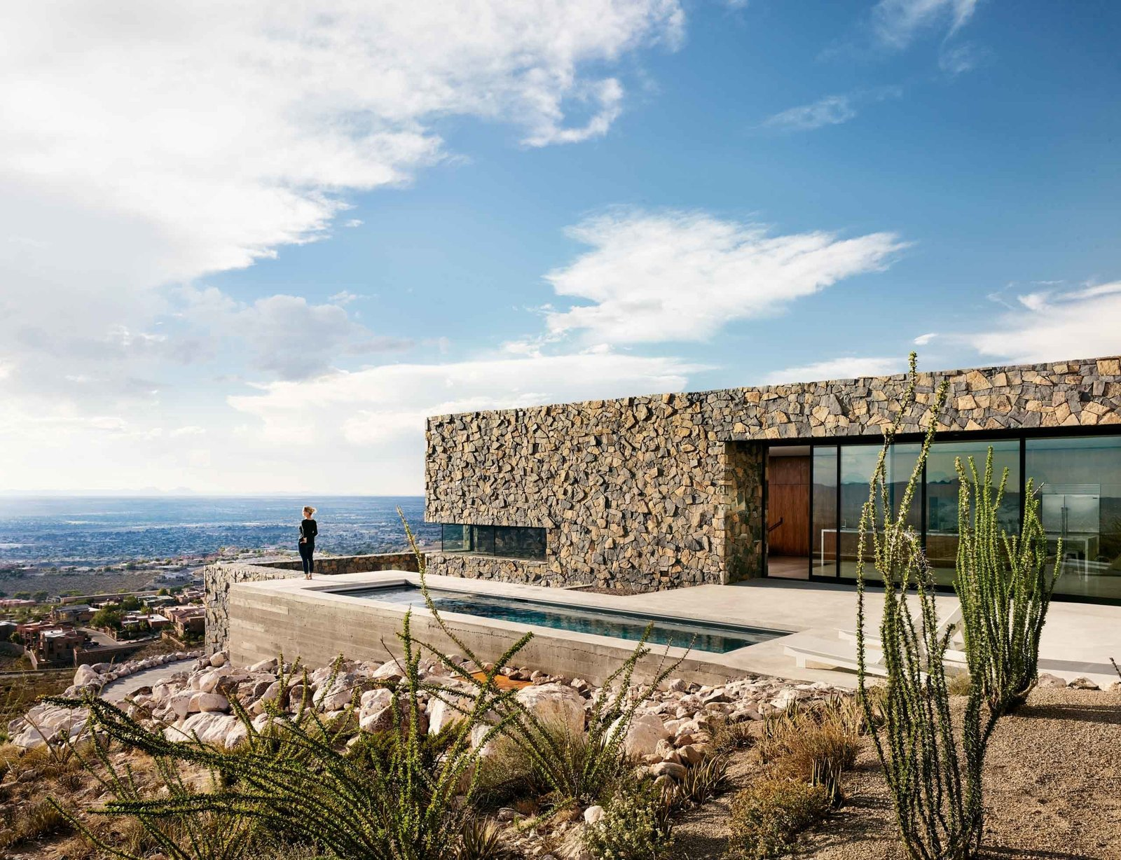 Swimming, Lap, Small, Concrete, Back Yard, Slope, Desert, Exterior, Stone, and House  The main level of the Franklin Mountain House is built with volcanic rock basalt and granite from the region.  Best Exterior Concrete Back Yard Photos from West Texas Vistas