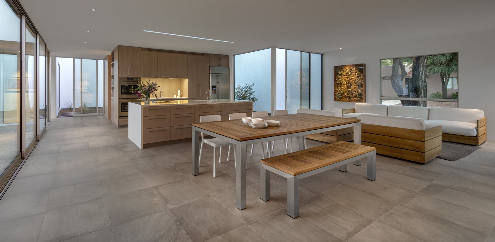 Metal, Sliding Door Type, Dining Room, Bench, Table, Ceiling Lighting, and Porcelain Tile Floor Huge panels of glass give the clients the ability to see into any number of the home's courtyards at once.  Custom Cat House