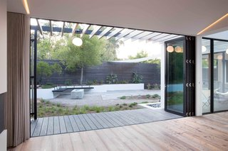 This giant bi-fold door opens up to a covered boardwalk-style walkway and the backyard.