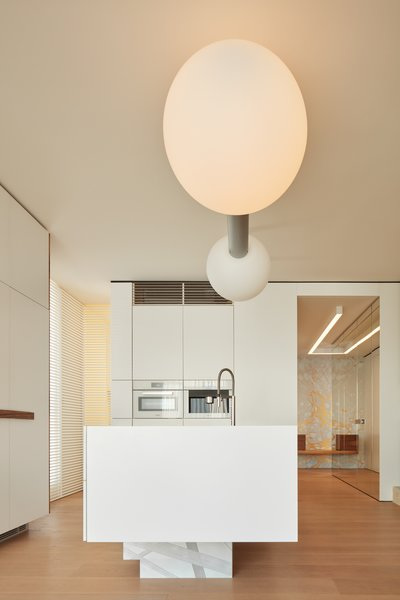 Casa Dolce Vita's brilliant white kitchen is a lesson in simplicity; Atelier Michael Hagara tucked all the appliances away neatly so certain features, like the pendant light, could shine.