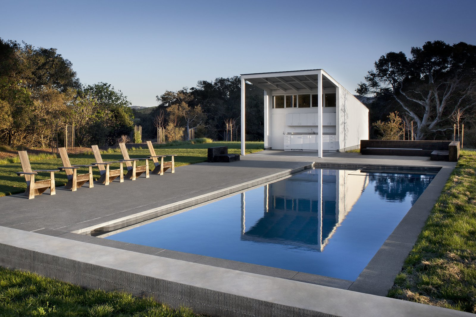 Outdoor, Trees, Grass, Swimming Pools, Tubs, Shower, Back Yard, Large Pools, Tubs, Shower, Large Patio, Porch, Deck, and Concrete Patio, Porch, Deck #TurnbullGriffinHaesloop #exterior #poolhouse #pool #kitchenette #landscape   Hupomone Ranch by Turnbull Griffin Haesloop Architects